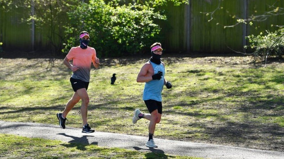 People wearing a mask run in Battersea Park on Sunday 5 April