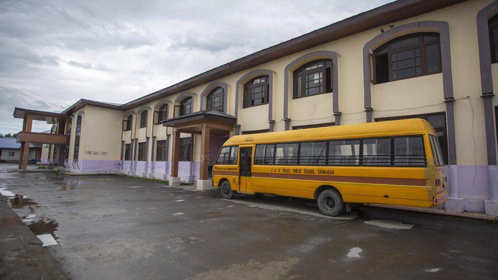 A school bus lies idle next to a school in Kashmir