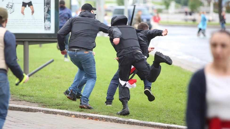 Unidentified people holding batons chase a man in an attempt to knock him down during an opposition rally to protest against police brutality and to reject the presidential election results in Minsk, Belarus September 6, 2020.