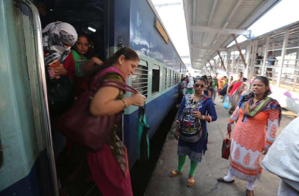 People mind the gap as they get off the train at Mumbai
