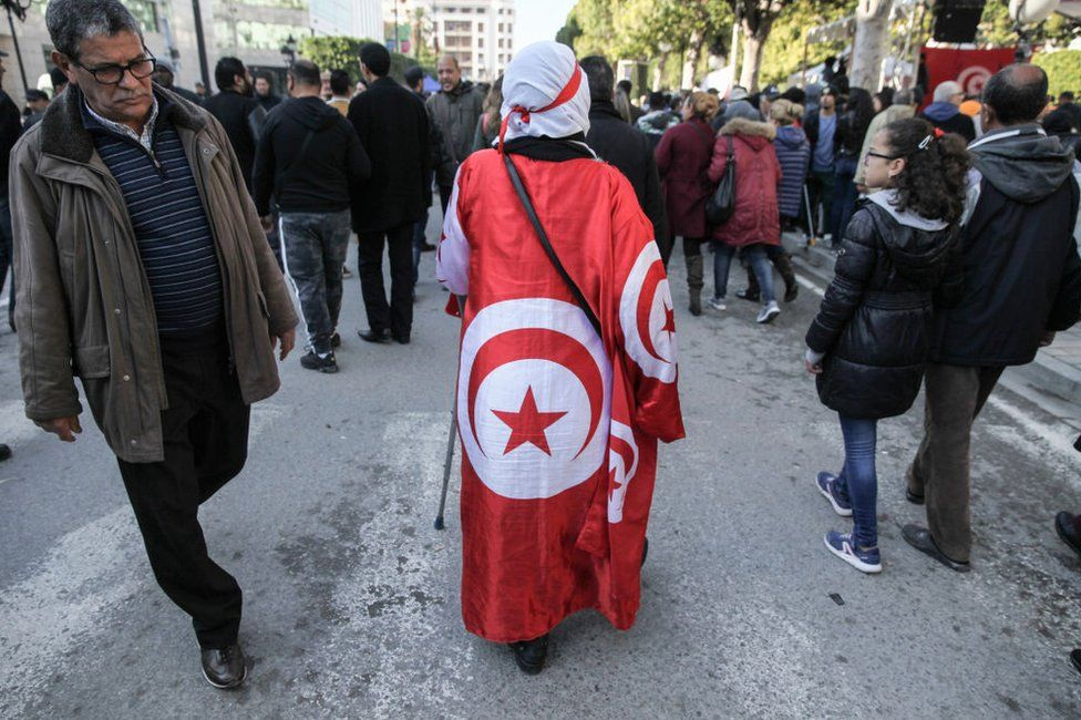 A woman draped in the national flag walks down a road on the anniversary of the 2011 Arab Spring.
