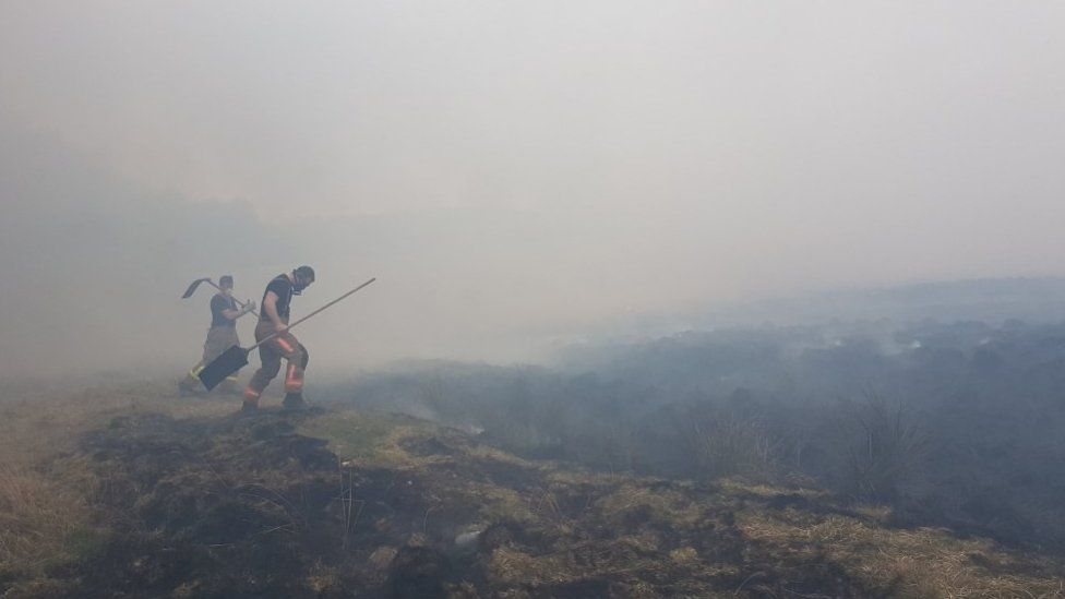 Firefighters tackling a blaze at Lyme Park