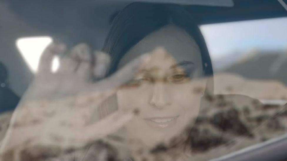 Woman traces landscape on car window