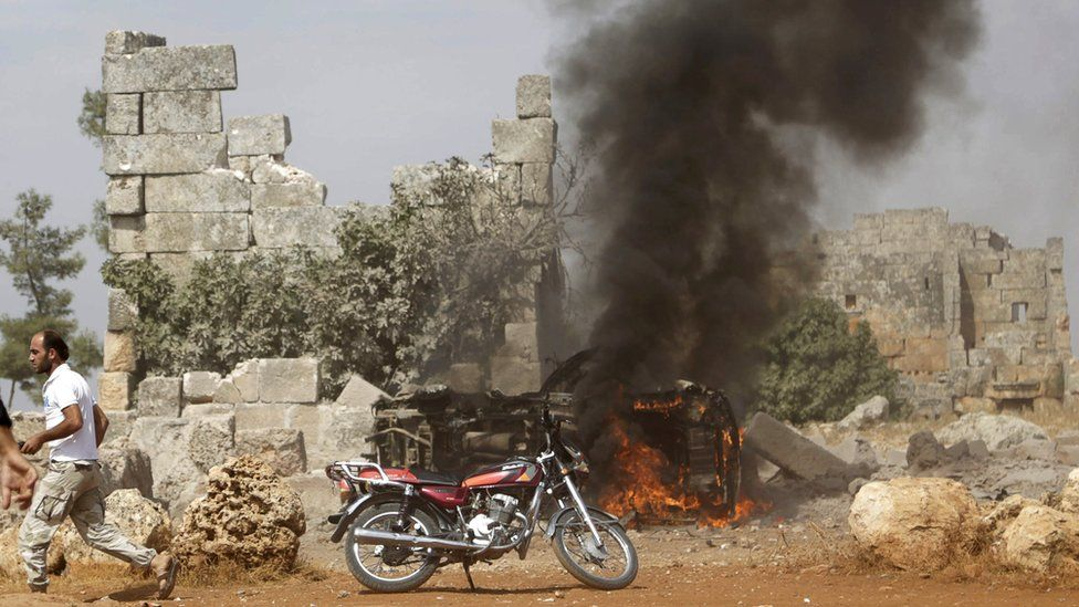 A man runs past a vehicle that rebel fighters say was targeted in a Russian air strike in Hass, in Idlib province, Syria (1 October 2015)