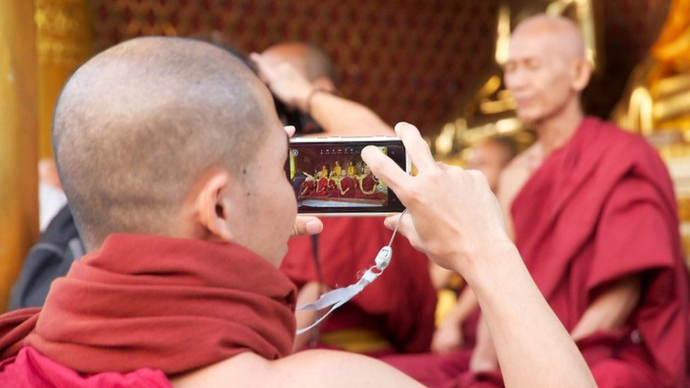 Buddhist monk taking photo on smartphone