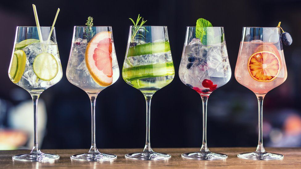 Five colourful gin tonic cocktails in wine glasses
