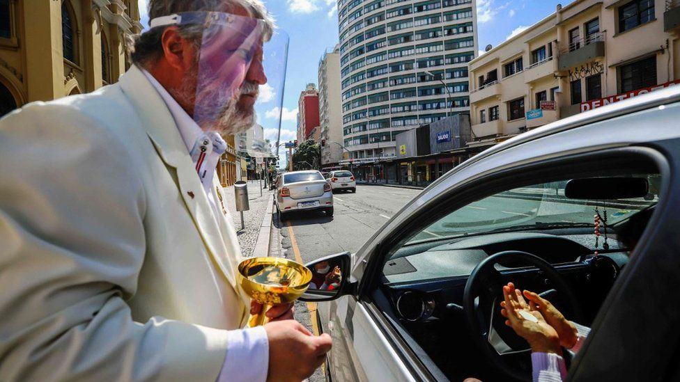 Minister Edilson Paes from the Basilica Cathedral wears a face shield as he gives communion in a drive-through ceremony during an Easter Sunday service during the coronavirus pandemic in Curitiba on 12 April 2020