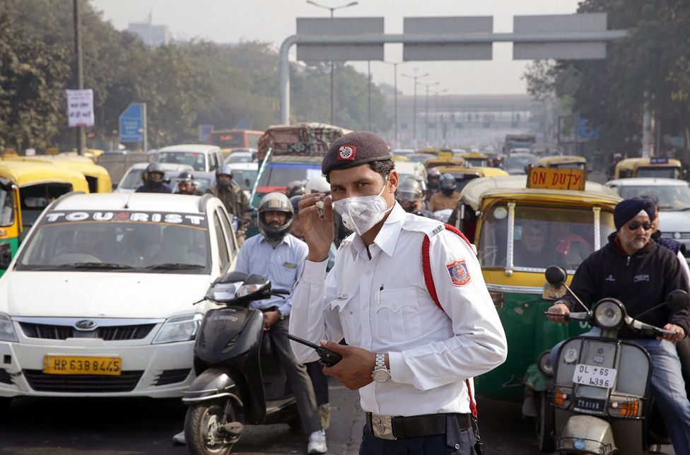 A traffic police man stands at traffic lights wearing a pollution mask during the first day of the implementation of the odd-even scheme for the vehicles in Delhi, India, 1 January 2016