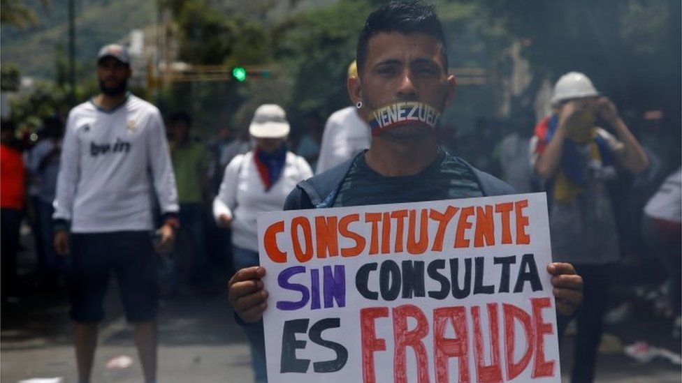 """A demonstrator with his mouth covered holds a sign that reads """"Constituent without consultation is fraud"""" while rallying against Venezuela's President Nicolas Maduro in Caracas, Venezuela June 5, 2017."""