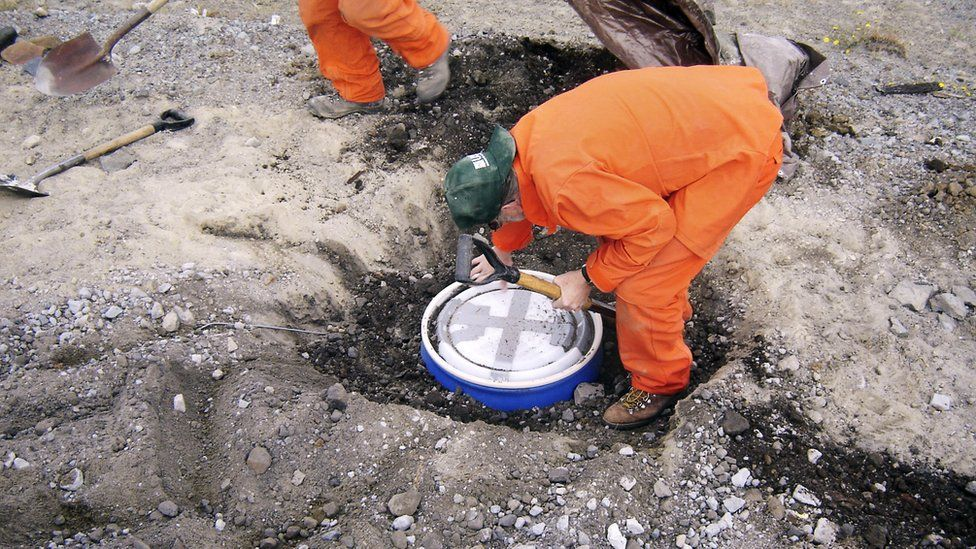 A scientist in an orange jumpsuit placing a round seismometer in a prepared hole in the ground