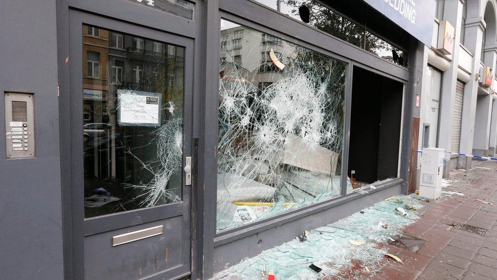 shop window riddled with holes, broken glass on the ground
