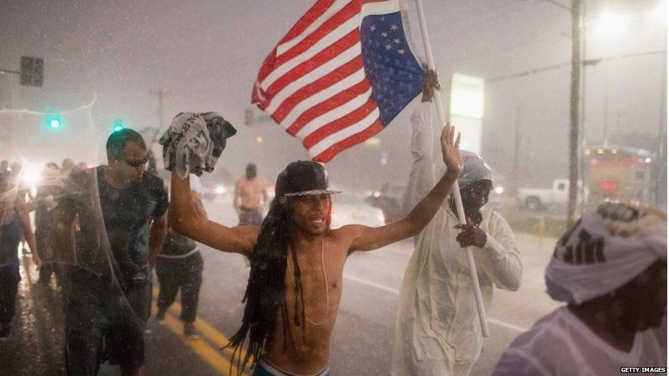 Demonstrators, marking the one-year anniversary of the shooting of Michael Brown, march along West Florrisant Street in a driving rain in Ferguson, Missouri (9 August 2015)