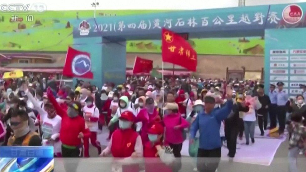 A large crowd of ultramarathon runners waving flags as they set off before disaster struck in Gansu, China on 22 May 2021