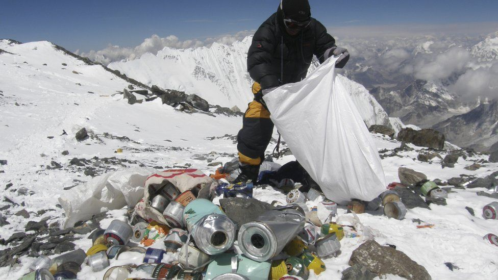 This picture taken on 23 May 2010 shows a Nepalese sherpa collecting garbage, left by climbers, at an altitude of 8,000 metres during the Everest clean-up expedition at Mount Everest.