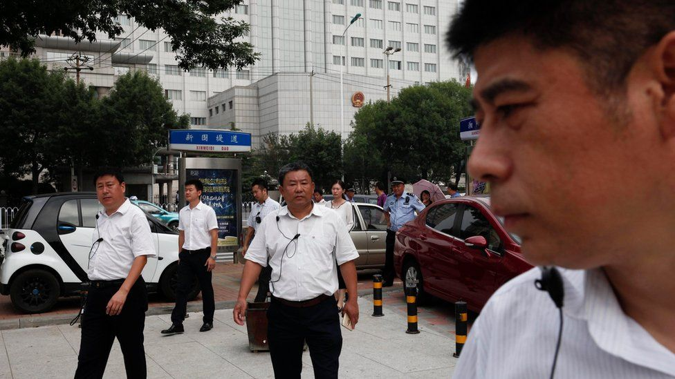 "Chinese men in plain clothes, believed to be security personnel, follow journalists in an apparent attempt to affect photo and video coverage outside The No.2 Intermediate People""s Court in Tianjin City, located northeast of Beijing, China, 04 August 2016"