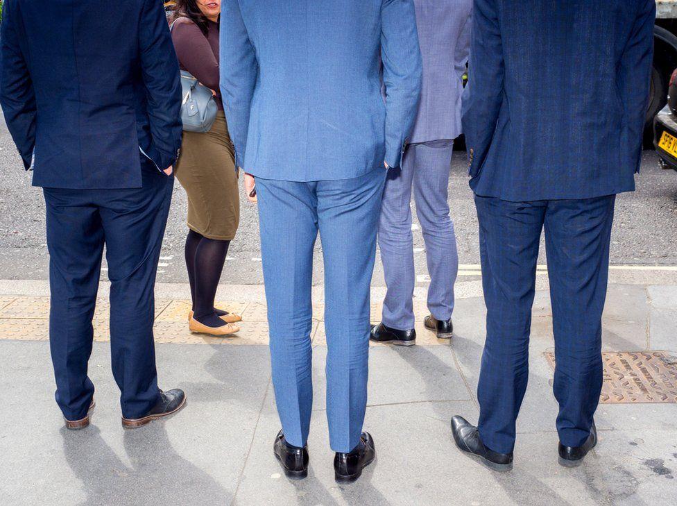 Men in suits wait to cross the road. St Paul's, London.
