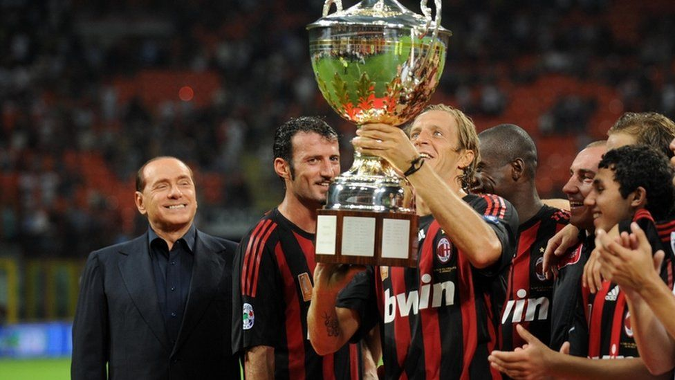 Berlusconi stands with AC Milan players holding up a trophy in 2008
