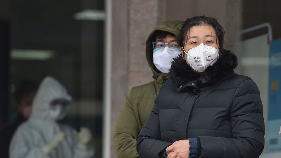 People in protective masks outside Wuhan Fifth Hospital