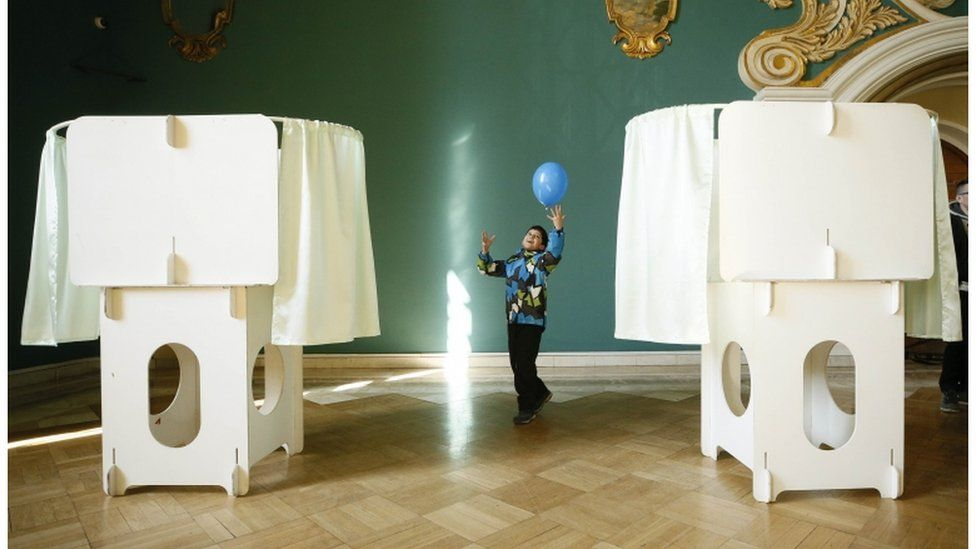 A child plays with a balloon near voting booths in Moscow