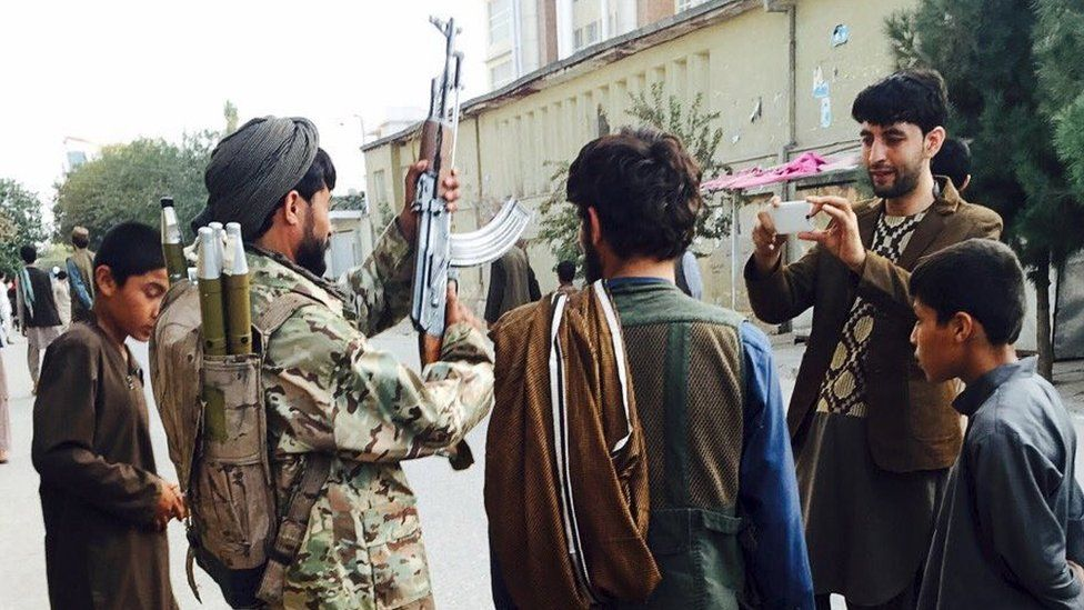 A Taliban fighter poses for a photo at the main square, a day after the insurgents took control of the strategic northern city of Kunduz