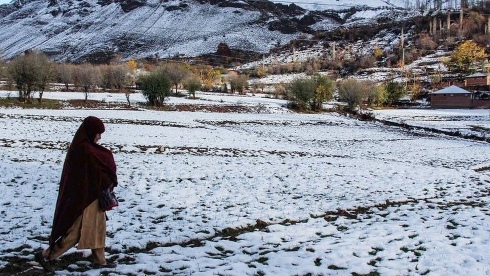An earthquake victim walks across a snow-covered field in the village of Charun Veer in Chitral valley, Pakistan (November 2015)