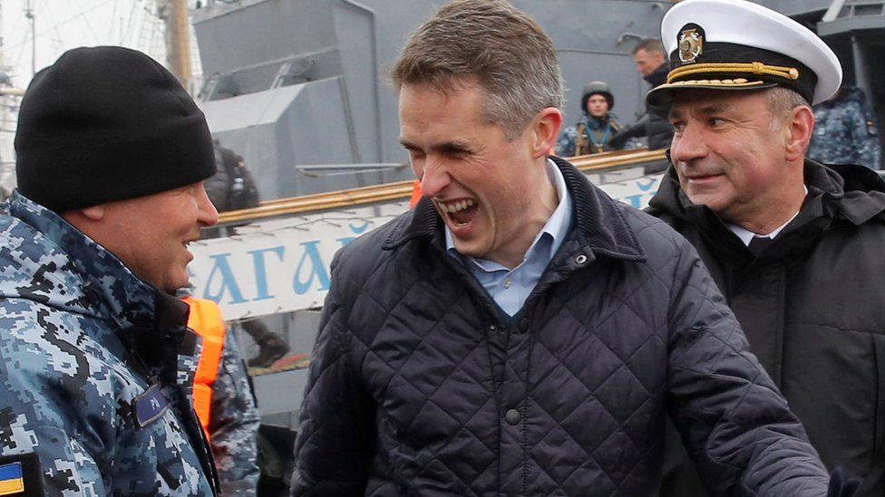 British Defence Minister Gavin Williamson (C) reacts during a meeting with Ukrainian navy sailors in Odessa