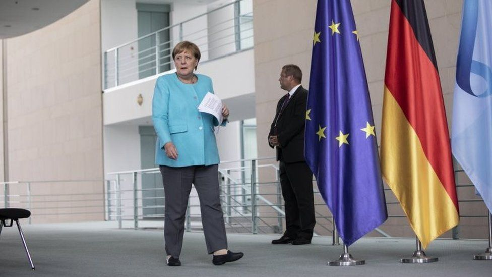 German Chancellor Angela Merkel (L) arrives to speaks to the media following a virtual meeting of the European Council, during the coronavirus pandemic in Berlin, Germany, 19 August 2020.