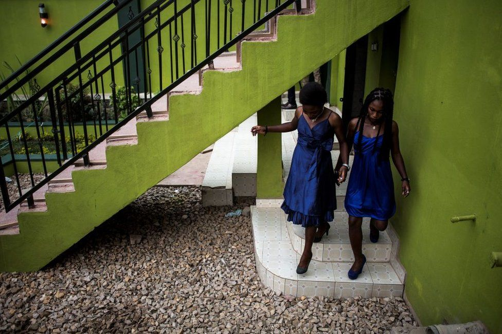 Two young women are seen ahead of a welcoming ceremony for first year students on February 3, 2018 in Beni.