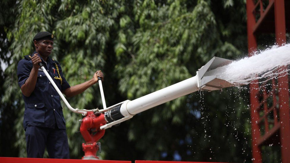 A law enforcement official sprays disinfectant in Abuja, Nigeria, on April 1, 2020.