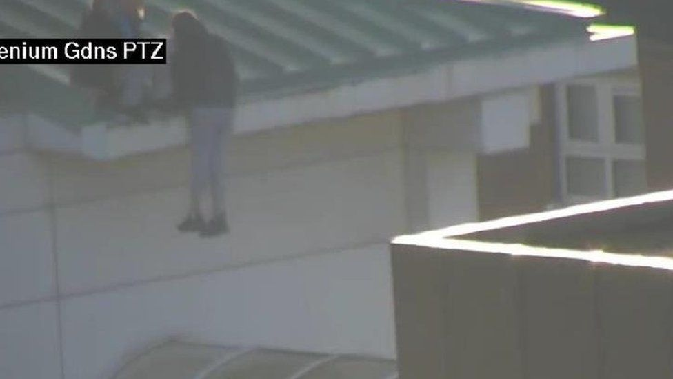 Youth hanging off roof