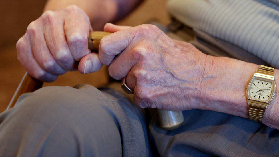 elderly person holding walking stick