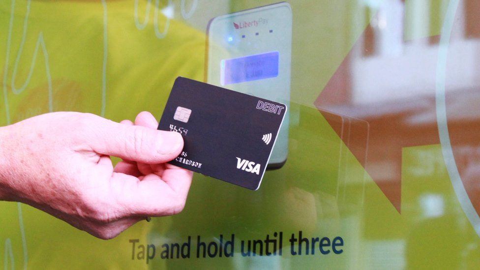 Hand holding a debit card to a contactless payment terminal
