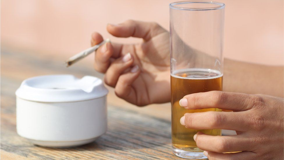 Hands holding a cigarette and drinking alcohol