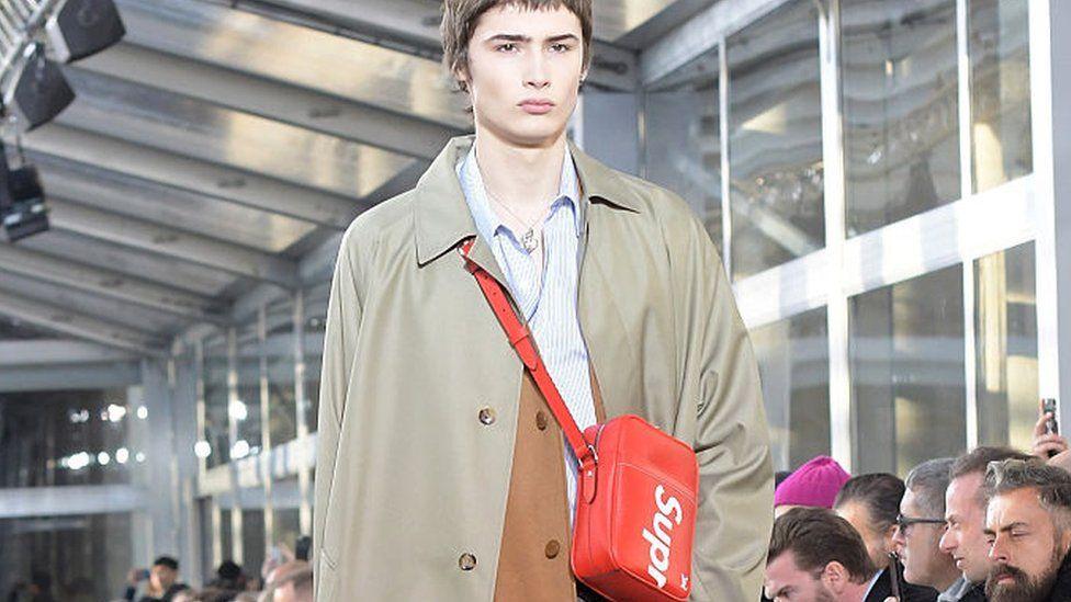 Male model wears bag on the Louis Vuitton catwalk