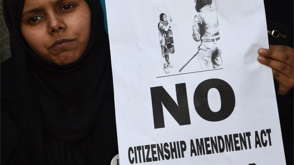 A woman holds a placard at a protest outside Jamia Millia Islamia university in New Delhi