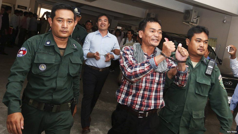 Supporters of the Cambodia National Rescue Party (CNRP), are escorted by Cambodian police officers at the Phnom Penh Municipal Court, 21 July 2015