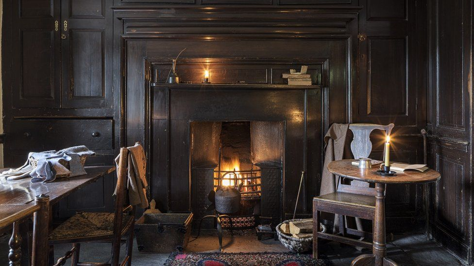 A fireplace, table and chairs in the restored Dove Cottage