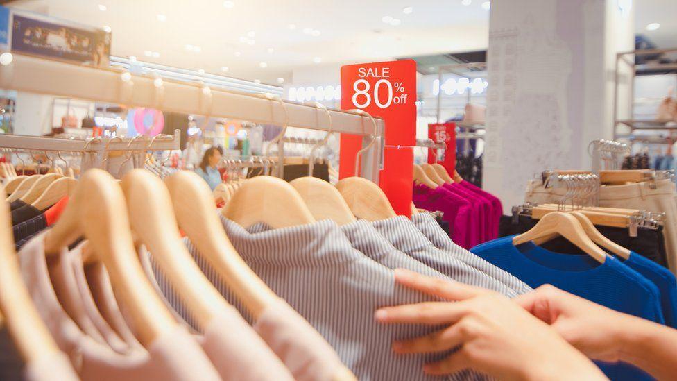 Shopper looks through sale rack