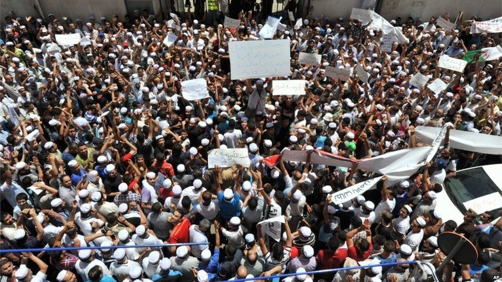 """Hundreds of demonstrators of the Berber community stage a protest in front of a walled area where Algier""""s newspapers are headquartered in support of Berbers in the southern Ghardaia region where at least 22 people have died in ethnic unrest, in Algiers, Algeria, Wednesday, July 8, 2015."""
