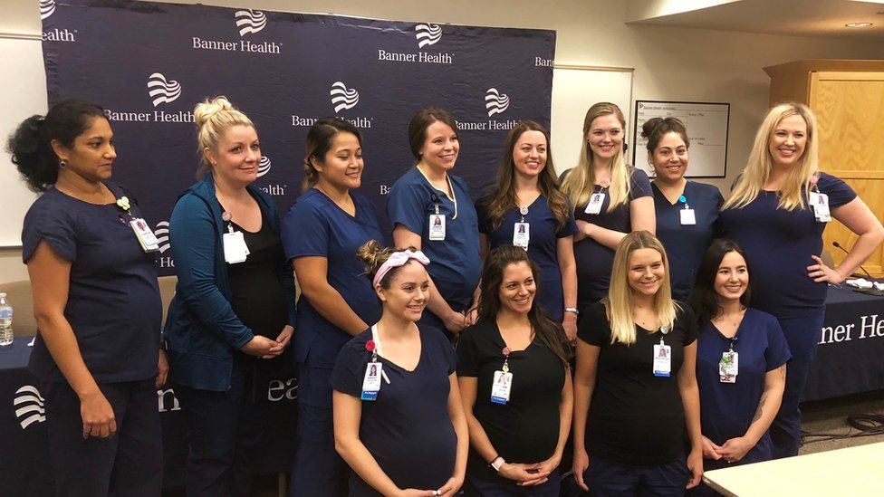 12 of the 16 pregnant nurses pose with their bumps on show in uniform