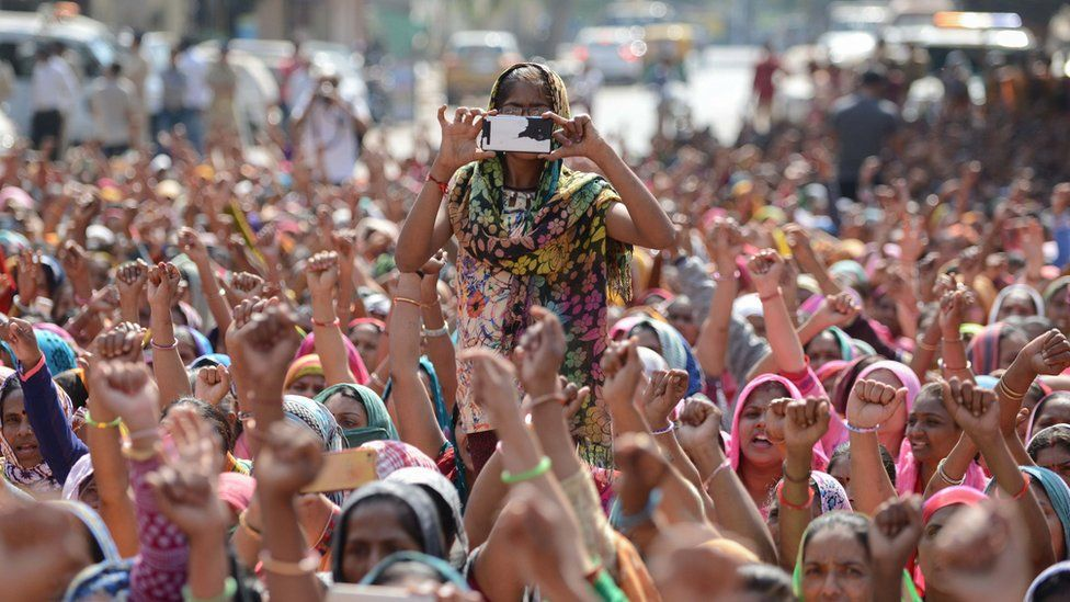A woman from an Indian workers' union takes photos on a mobile phone during a protest in Ahmadabad on February 12, 2017.