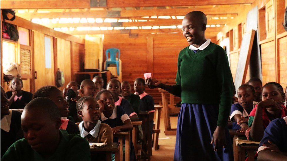 A girl holds up a cup in a class room at one of Ruby Cup's African projects