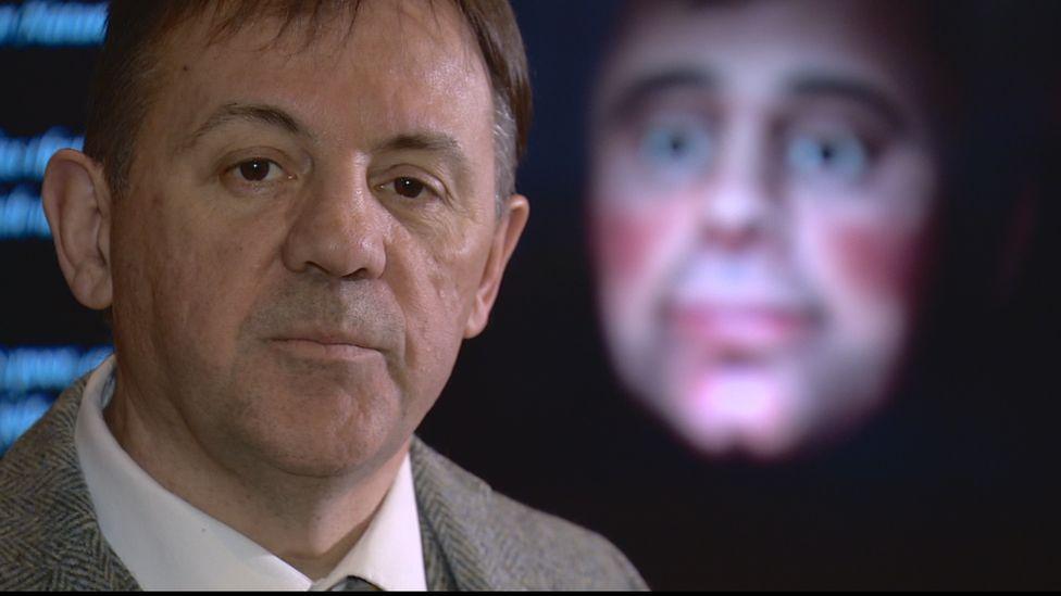 Poet Rab Wilson standing next to the 3D digital model of Robert Burns