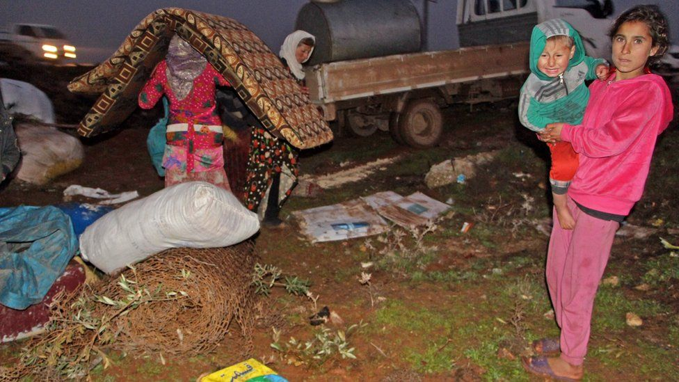 A displaced Syrian family unpacks their belongings at a makeshift camp near the town of Binnish, in Idlib province (5 February 2020)