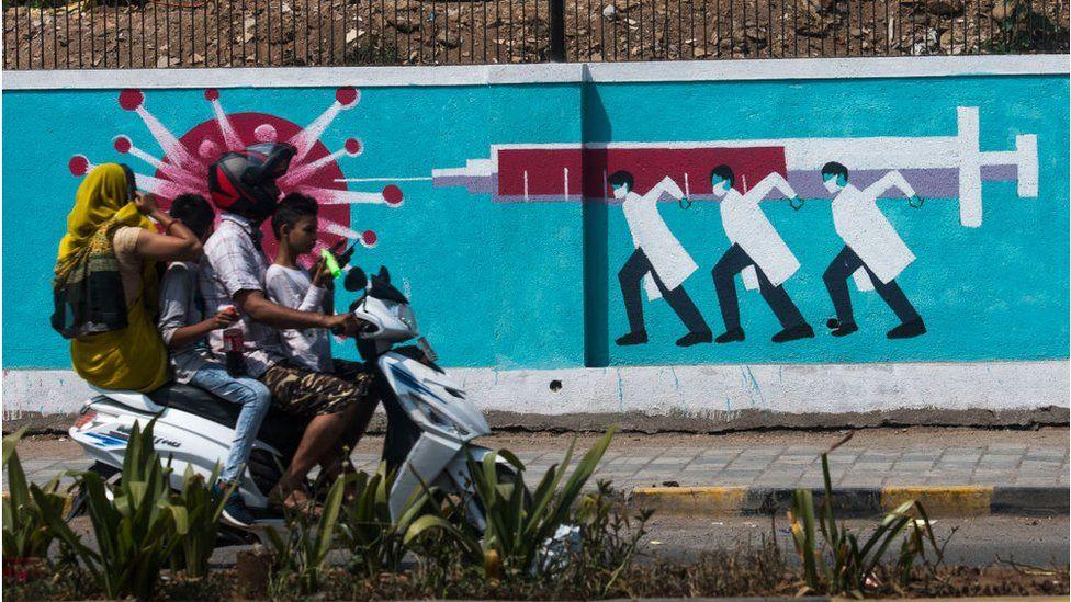 Люди проходят мимо настенной росписи, изображающей медицинский персонал, поражающий корону вакцинной иглой