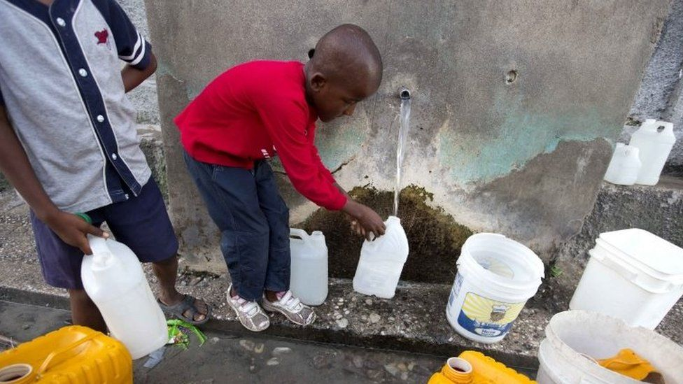 Residents collect water from a well in Les Cayes, Haiti.