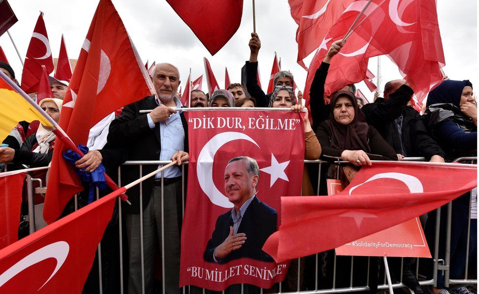 """Turkish people protest with a picture of president Erdogan during a demonstration against the Turkey coup attempt in support of Turkey""""s president Erdogan in Cologne, Germany, Sunday, July 31, 2016"""