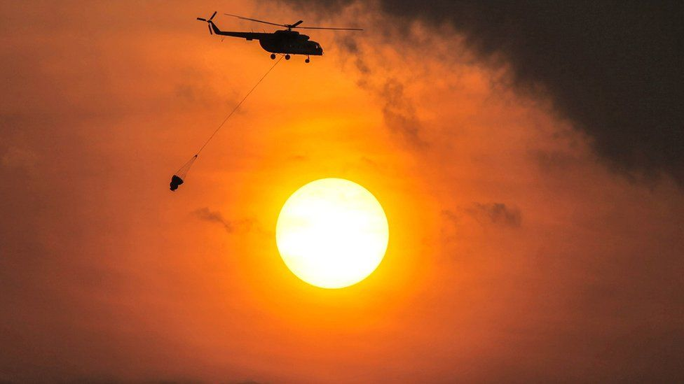 A helicopter carries water to extinguish a land fire in South Sumatra