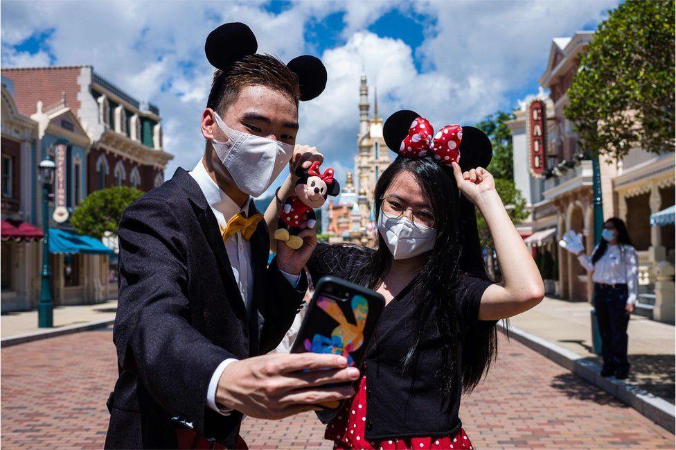 Visitors dressed in costumes take a selfie at Hong Kong's Disneyland