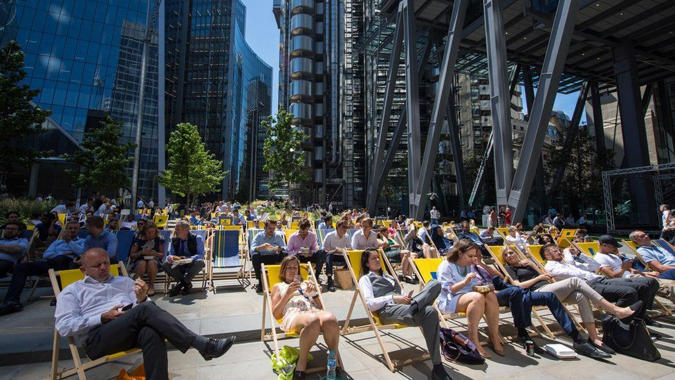 People enjoy their lunch break in the sun in the City financial district of London